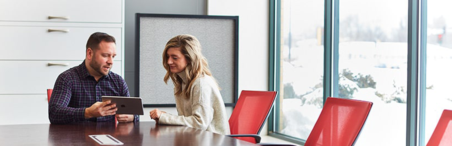 A man and woman collaborating in a conference room with modern red chairs