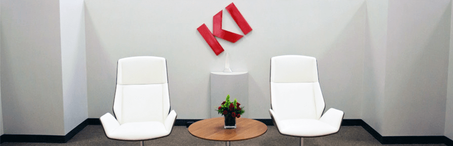 Two white modern chairs in a lobby with the KI logo on the wall behind them